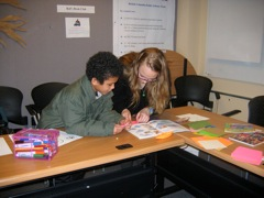 Larkyn helping a student with origami.